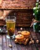 Bananenkleiner kuchen auf einem hölzernen Stand Transparentes Cup mit grünem Tee Lizenzfreie Stockbilder