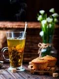 Bananenkleiner kuchen auf einem hölzernen Stand Transparentes Cup mit grünem Tee Stockfoto
