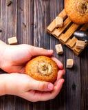 Bananenkleiner kuchen in den Händen von Kindern auf einem hölzernen Hintergrund Lizenzfreie Stockfotos