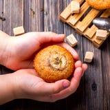 Bananenkleiner kuchen in den Händen von Kindern auf einem hölzernen Hintergrund Lizenzfreies Stockfoto