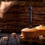Bananenkleiner kuchen mit einem Löffel, Stücke Zucker nahe Hölzernes backgr Stockfotos