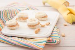 Bananenscheiben mit Erdnussbutter auf weißem Brett Stockfotos