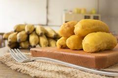 Bananenstückchen auf hölzernem hackendem Brett Stockfotos