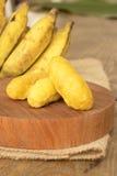 Bananenstückchen auf hölzernem hackendem Brett Lizenzfreie Stockbilder