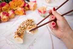 Bananensushi servered mit Nüssen und Granola auf einer Glasplatte Stockbilder