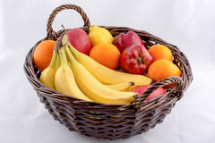 Bananer, apelsiner, äpplen och citroner i en vide- korg Arkivbilder