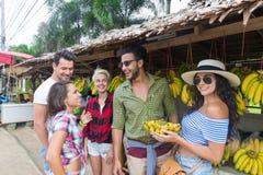 Bananer för folkgruppköpande på traditionell marknad för gata, ung man och kvinnahandelsresande Royaltyfri Fotografi
