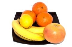 Bananer, grapefrukt, citron och apelsin på en svart platta Arkivfoton