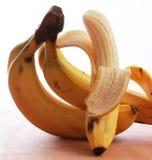 Bananer grupp av fem med ett skalat öppet Royaltyfri Bild