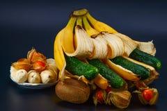 Bananer gurkor, fizalis, kiwi på en mörk bakgrund royaltyfri foto