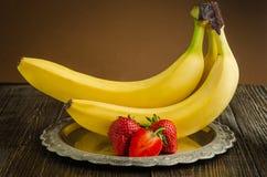 Bananer med jordgubbar på en tappningplatta Arkivbilder