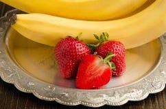 Bananer med jordgubbar på en tappningplattacloseup Royaltyfria Foton