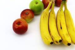 Bananer och äpplen mötte på vit bakgrund arkivbilder