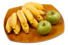 Bananer och äpplen på maträtten Fotografering för Bildbyråer
