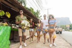Bananer och ananas för folkgrupp hållande på traditionell marknad för gata, ung man och kvinnahandelsresande Arkivfoto