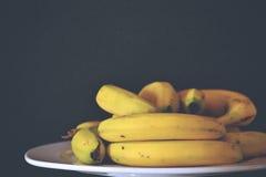 Bananer på den vita plattan Arkivbild