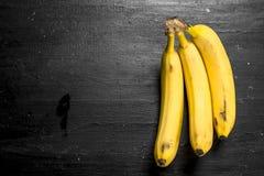 bananer samlar ihop moget På den svarta svart tavlan Arkivbilder