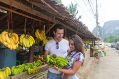 Bananes de achat de couples sur le marché de rue, le jeune homme et les voyageuses traditionnels de femme Photo stock