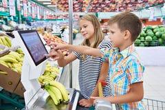 Bananes de achat de garçon et de fille dans la boutique Photos stock