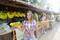 Bananes et ananas de prise de femme sur le marché de rue, le jeune homme et les voyageuses traditionnels de femme Image stock