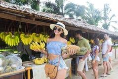Bananes et ananas de prise de femme sur le marché de rue, le jeune homme et les voyageuses traditionnels de femme Image libre de droits