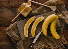 Bananes et tranches de banane sur un conseil en bois Images libres de droits