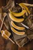 Bananes et tranches de banane sur un conseil en bois Photographie stock libre de droits