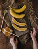 Bananes et tranches de banane sur un conseil en bois Image stock