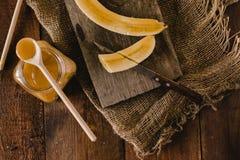 Bananes et tranches de banane sur un conseil en bois Photographie stock