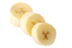 Bananes fraîchement coupées en tranches sur un chemin de coupure blanc de fond Image libre de droits