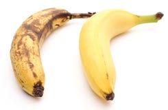 Bananes fraîches et trop mûres sur le fond blanc Photo libre de droits