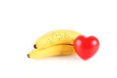 Bananes mûres avec la forme de coeur d'isolement sur le blanc Image stock