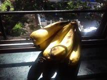 Bananes op venster Stock Afbeeldingen