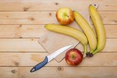 Bananes, pommes, couteau et un plat en bois de coupe sur un fond en bois Photographie stock libre de droits