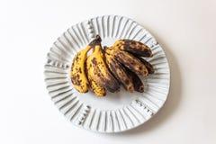 Bananes trop mûres de bébé d'un plat blanc cannelé, d'isolement sur le blanc images stock