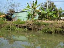 Bananiers et un bâtiment le long de la voie d'eau du delta du Mekong Photos libres de droits
