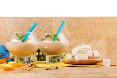 Bananmilkshakar på en vit bakgrund Exotiska efterrätter Turkisk fröjd och smoothies på en tabell kopiera avstånd Arkivbild
