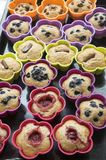 Bananmuffin med choklad, blåbär, jordgubbar, muttrar och russin i silikonformer på på den svarta bakplåten Royaltyfri Foto