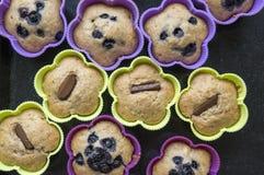 Bananmuffin med choklad, blåbär, jordgubbar, muttrar och russin i silikonformer på på den svarta bakplåten Royaltyfri Bild