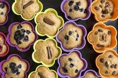 Bananmuffin med choklad, blåbär, jordgubbar, muttrar och russin i silikonformer på på den svarta bakplåten arkivfoton