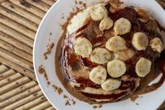 Bananowa czekoladowa naleśnikowa odgórnego widoku fotografia Naleśnikowy śniadanie na drewnianym stole Bananowy czekoladowy deser Fotografia Stock