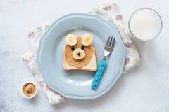 Bananowa masło orzechowe grzanka na błękitnym talerzu, posiłek dla dzieciaków Zdjęcia Stock