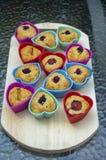 Bananowi muffins z czekoladą, czernicami, truskawkami, dokrętkami i rodzynkami w krzem foremkach na drewnianej macie, kolorowi se fotografia stock