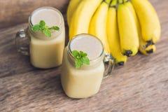 Bananowi smoothies i banany na starym drewnianym tle Fotografia Royalty Free