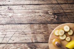 Bananowy i pokrojony banan w kawałki z miodem na drewnianym tle, kopii przestrzeń obrazy stock