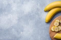 Bananowy i pokrojony banan w kawałki z miodem na textured tle, kopii przestrzeń fotografia stock