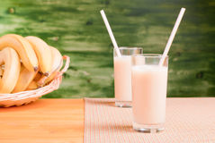 Bananowy sok w dwa filiżankach na koloru żółtego stole z pieluchą na zale Zdjęcie Stock