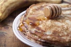 Bananpannkakor med honung på en platta Royaltyfria Foton