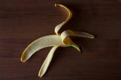 Bananskal på en brun trätabell arkivfoto