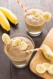 BananSmoothie på träbakgrund Top beskådar Arkivfoto